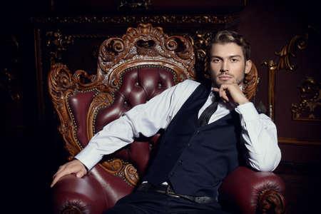 Imponente hombre bien vestido sentado en un sillón en un lujoso apartamento con interior clásico. Lujo. Belleza masculina, moda. Foto de archivo
