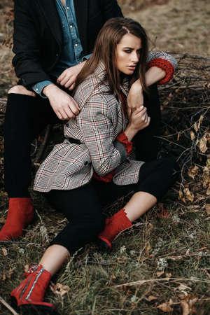 秋のファッション。黄色い秋の草と葉の美しいファッショナブルなカップル。