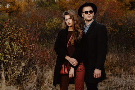 Portrait of a beautiful young people walking in the autumn park. Autumn fashion.