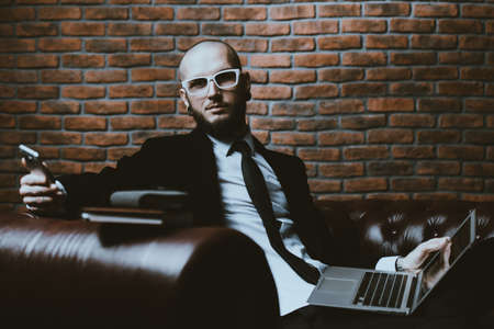 Young brutal businessman is working at home using his laptop and smartphone. Male beauty, fashion. Business concept. Modern technologies. Stok Fotoğraf