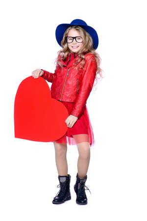 Full length portrait of a pretty pre-teen girl holding big red heart. Isolated over white. First love. Valentine's Day.  Banco de Imagens