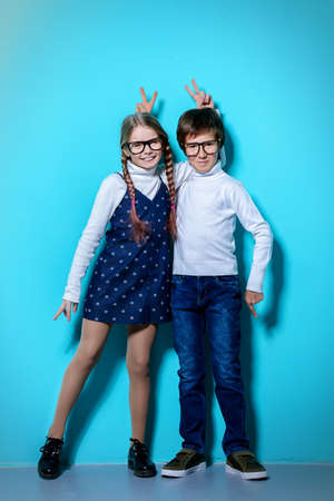 Childrens fashion. Happy boy and girl posing together at studio. Education.