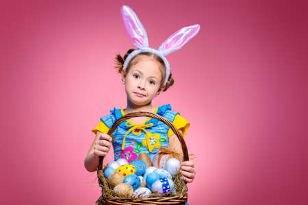 Easter holiday. Portrait of a happy little girl wearing bunny ears with basket full of painted eggs over pink background.