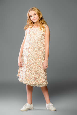 Childrens fashion. Cute nine year old girl with long blonde hair posing in summer dress. Studio shot. Full length portrait. Stockfoto