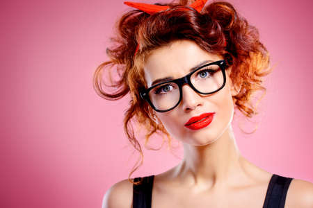 Portrait of a funny smart girl wearing in glasses with curly foxy hair and a red bow on hair. Pin-up retro style.