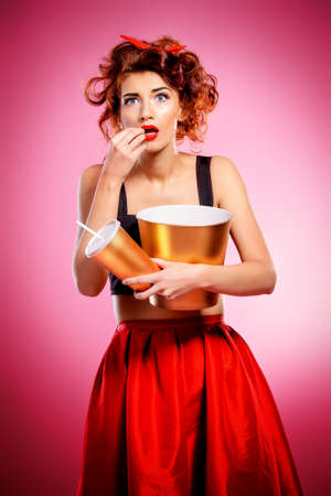 Pretty emotional young woman eating popcorn and drinking soda over pink background. Pin-up style. Entertainment and cinema concept.