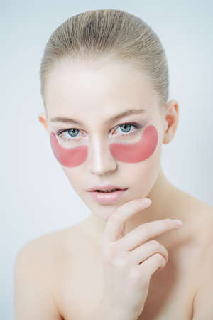 Young beautiful woman with collagen pads under her eyes on a white background. Spa, eye skin care.