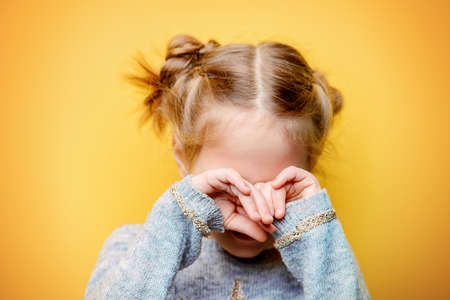 Close-up portrait of an offended crying little girl. Yellow background. Childhood concept. Stock Photo