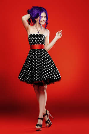 Beautiful girl with purple hair in a polka-dot dress posing on a red background. Beauty, fashion. Pin-up style.