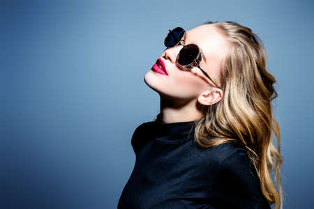 Attractive blonde young woman wearing black sunglasses. Studio shot. Beauty, fashion concept. Optics style.