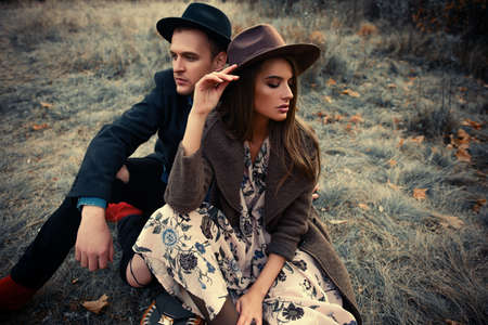 Autumn fashion. Beautiful fashionable couple on yellowed autumn grass and leaves.