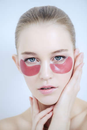 Young beautiful woman with collagen pads under her eyes on a white background. Spa, eye skin care. Foto de archivo - 97379930
