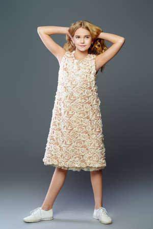 Childrens fashion. Cute nine year old girl with long blonde hair posing in summer dress. Studio shot. Stockfoto
