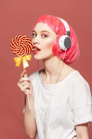 Trendy girl with pink hair wearing headphones is eating lollipop. Pink background. Youth style, leisure. Foto de archivo - 97447284