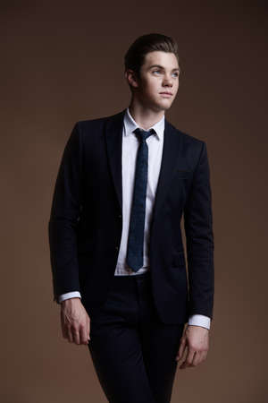 Handsome young man in elegant suit posing over brown background. Business style. Male beauty, fashion. Hairstyle.