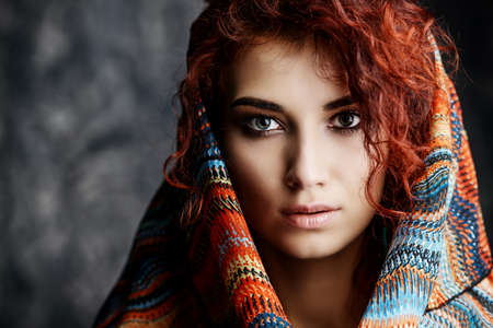 Close-up portrait of a beautiful red-haired woman wears a kerchief and earrings in boho style. Ethnic style in accessories. Фото со стока