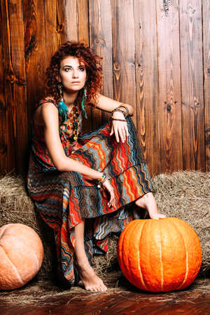 Beautiful bright woman with curly foxy hair sits on a haystack. Dress and accessories in boho style. Ethnic style in clothes. 写真素材