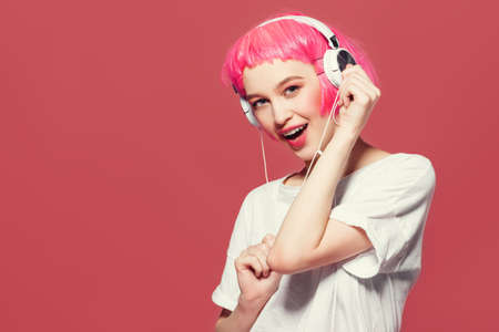 Trendy girl with pink hair enjoys the music on headphones. Pink background. Youth style, leisure. 스톡 콘텐츠