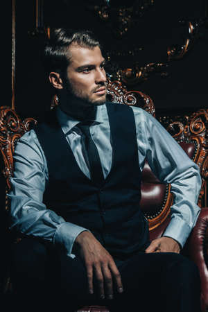 Imposing well dressed man in a luxurious apartments with classic interior. Luxury. Mens beauty, fashion. 스톡 콘텐츠