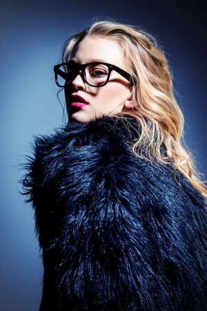 Attractive young woman in spectacles and fur coat. Studio shot. Beauty, fashion concept. Optics style.
