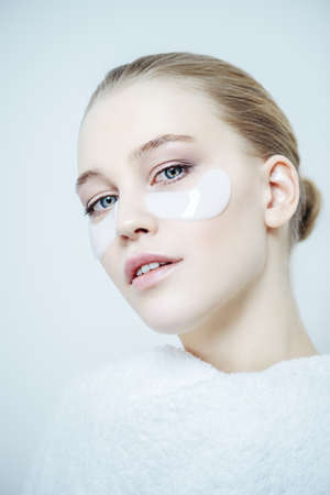 Close-up portrait of a beautiful young woman with collagen pads under her eyes on a white background. Spa, eye skin care. Foto de archivo - 97856464