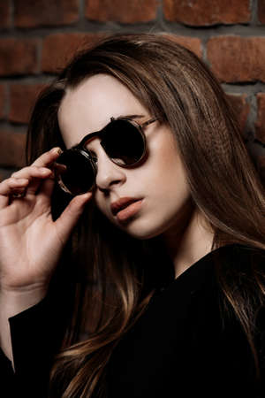 Modern young woman with shiny long hair in sunglasses standing by a brick wall. Beauty, fashion concept.