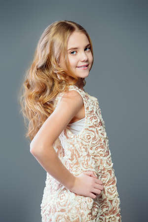 Children's fashion. Cute nine year old girl with long blonde hair posing in summer dress. Studio shot.