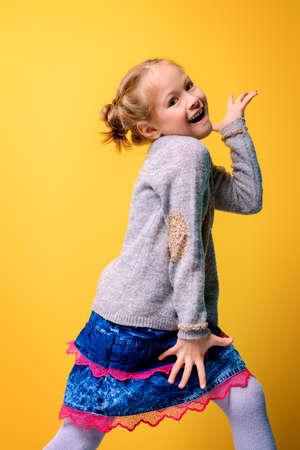 Kids fashion. Portrait of a cute six year old girl wearing knitted clothes posing over bright yellow background. Spring, winter fashion. Happy child girl.