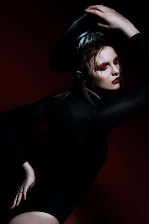 Sexual young woman with creative bright makeup, dressed in black body suit and a cap of police officer. Portrait over red background. Beauty, fashion.