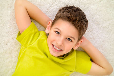 Joyful smiling child boy lying on a carpet and having a rest at home. Happy childhood. Stock Photo