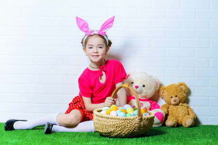 Cute happy little girl wearing bunny ears sits with Easter eggs on a green grass. Kids fashion. Easter holidays.
