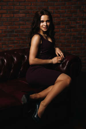 Attractive young woman posing on a leather sofa in elegant burgundy dress. Beauty, fashion. Loft style interior. Banque d'images - 98369919