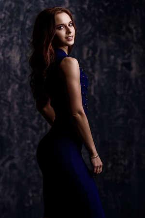 グランジの背景の上に青いタイトなドレスを着てポーズをとる美しい姿を持つ若い女性。