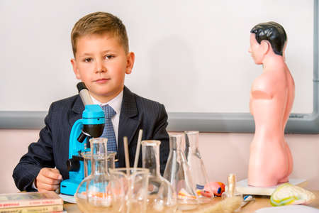 Schoolboy looking in the microscope during the lesson of chemistry or biology in school. Educational concept.