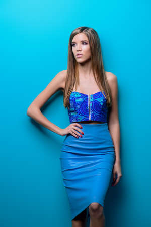Beautiful girl in elegant clothes posing over blue background. Beauty, fashion. Reklamní fotografie