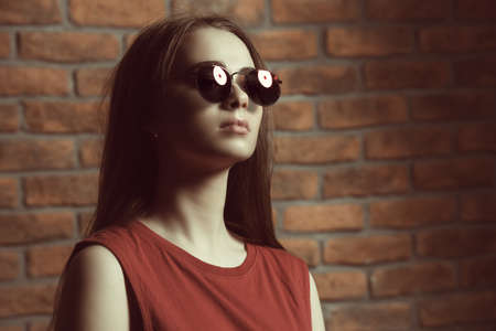 Attractive young woman in sunglasses and red t-shirt stands by a brick wall. Beauty, fashion concept.
