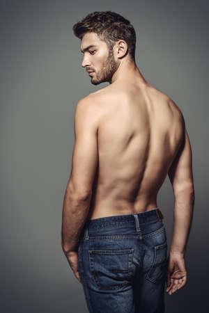 Porträt eines sexy jungen Mannes mit dem muskulösen Körper, der am Studio aufwirft. Grauer Hintergrund. Männer Gesundheit.