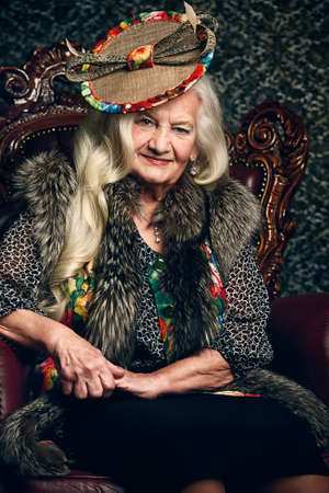 Fashionable old woman with beautiful blonde hair and elegant hat posing in vintage interior. Beauty, fashion. Retro style. Reklamní fotografie
