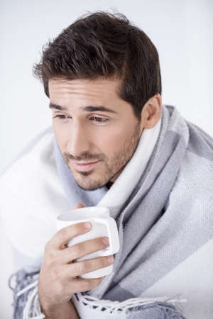 Sick young man wrapped in a blanket with a cup of tea looking at camera. Mens health. Stock Photo