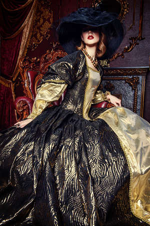 Portrait of a beautiful young woman in the lush expensive dress and elegant broad-brimmed hat in an old palace interior. Vintage style. Fashion. Renaissance Style.  免版税图像