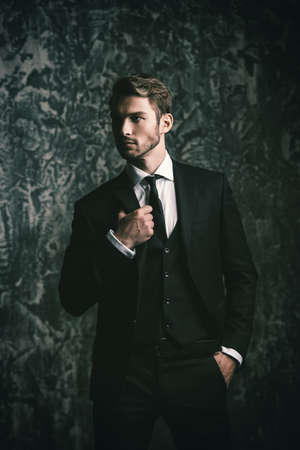 Portrait of a handsome man in an elegant suit on a grunge background. Studio shot. Stock Photo