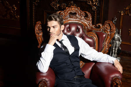 Imposing well dressed man in a luxurious apartments with classic interior. Luxury. Men's beauty, fashion.