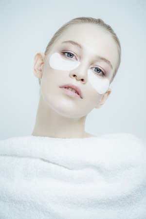 Close-up portrait of a beautiful young woman with collagen pads under her eyes on a white background. Spa, eye skin care. Stock Photo
