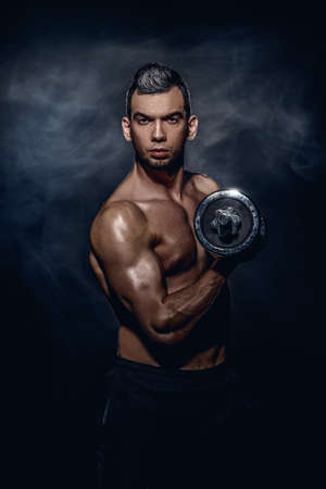 Muscular brutal man doing exercises with dumbbells. Health and sports concept.