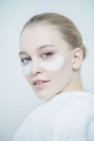 Close-up portrait of a beautiful young woman with collagen pads under her eyes on a white background. Spa, eye skin care. 写真素材
