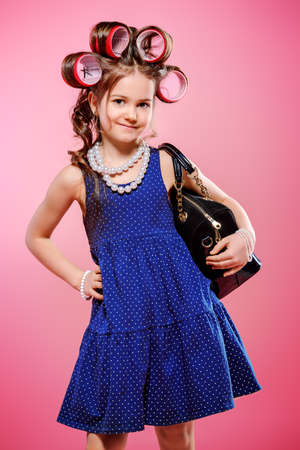 Portrait of a pretty little girl with curlers in her hair holding a bag. Studio shot over pink background. Kid's fashion.