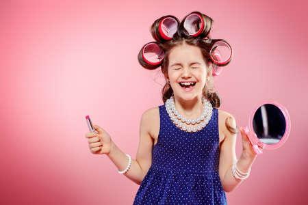 Portret van een mooi klein meisje met krulspelden in haar haar met lippenstift en spiegel. Studio opname over roze achtergrond. Kindermode.