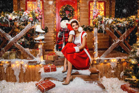 Pretty Santa girl is posing with a snowman near the house of Santa, decorated with festive lights. Christmas and New Year concept. Stock Photo