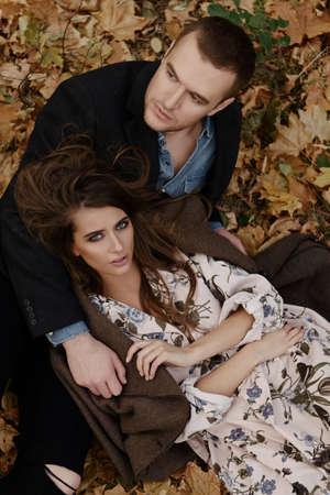 秋のファッション。黄色い秋の草や葉の上に横たわっている美しいファッショナブルなカップル。 写真素材