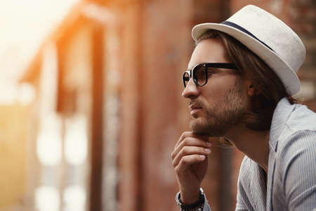 Close-up portrait of a smiling hipster man on a city street. Outdoor fashion.  Stock Photo